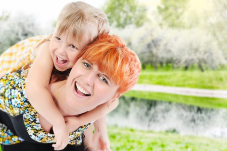 Funny girl hugs her young mother in the park photo