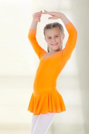 Little beautiful ballerina dancing in an orange dress. photo