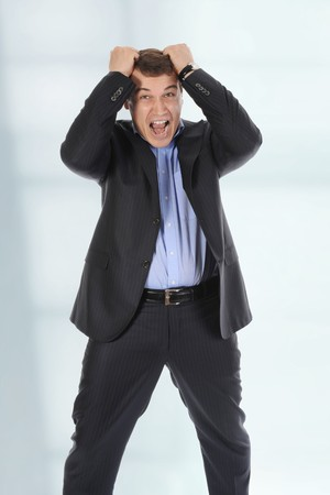 Infuriated businessman holding his head in a bright office photo