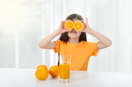 girl at the table with oranges and juice.  photo