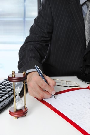 Businessman signs a document at the office at the workplace photo