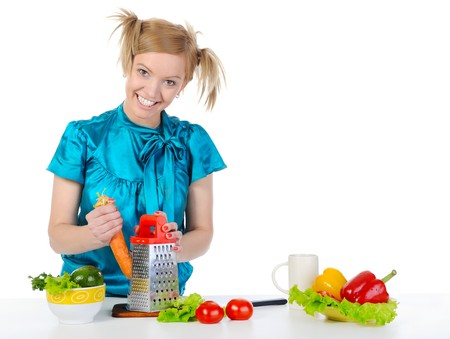 young girl in the kitchen rubbing carrots. Isolated on white background  photo