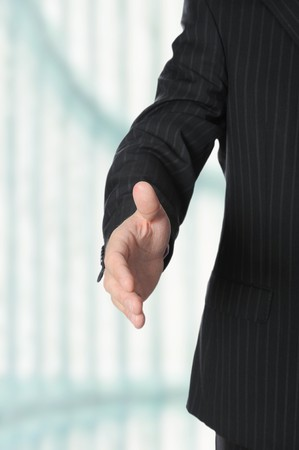 Businessman holds out his hand for a handshake.  photo