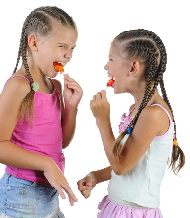Two smiling girls with candy. Isolated on white background photo