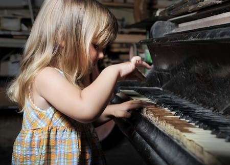 girl playing on an old piano. Isolated on white background photo