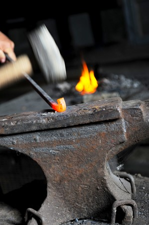 blacksmith forges iron in the forge photo