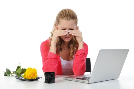 Weeping woman at a computer. Isolated on white background photo