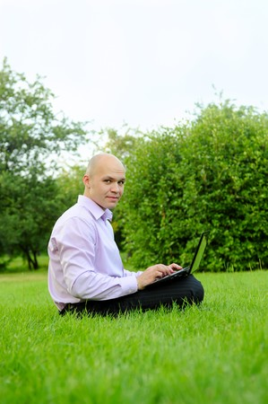 Businessman with laptop on the green grass in the park photo