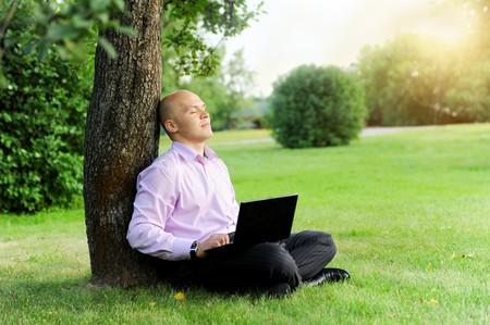 Businessman with laptop sitting near a tree in the park Stock Photo - 7539648