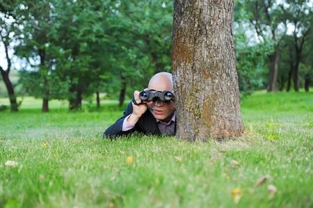 Businessman in the green park looking through binoculars photo
