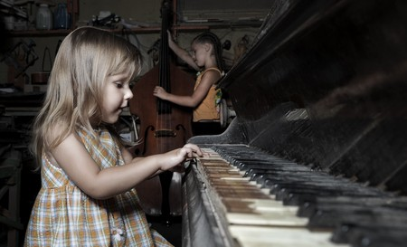 girl playing on an old piano in an abandoned building photo