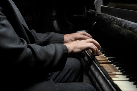 Hands of the musician on the keyboard of an ancient grand piano photo