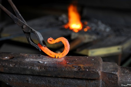 Incandescent element in the smithy on the iron anvil photo