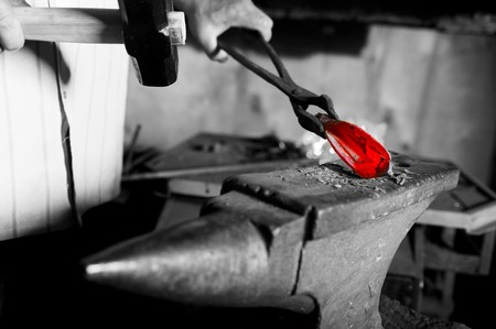 smithery: blacksmith in the smithy manufactures decorative element of iron Stock Photo