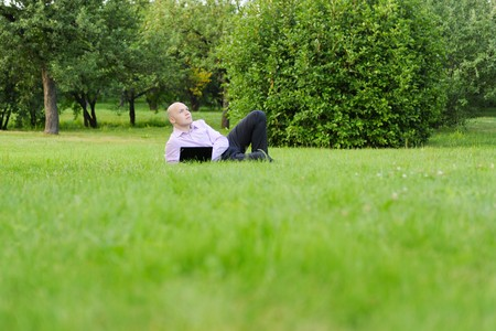 man with laptop lying on green grass in the park photo