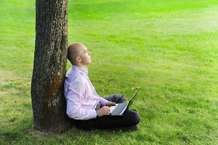man with laptop sitting near a tree in the park photo