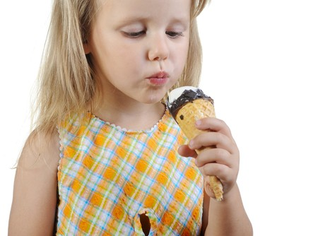 Little girl eating ice cream. Isolated on a white background photo