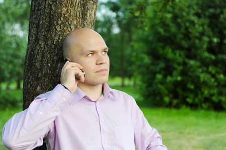 man in a green park talking on the phone Stock Photo - 7603837