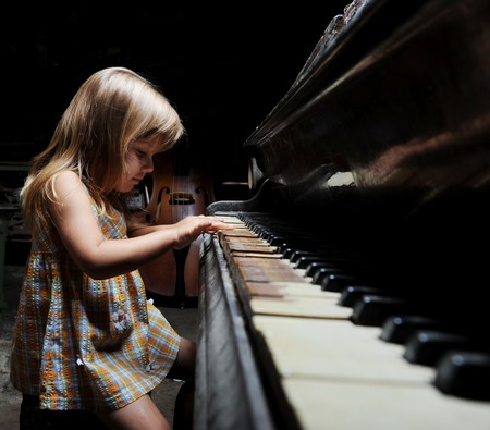 girl playing on an old black piano photo
