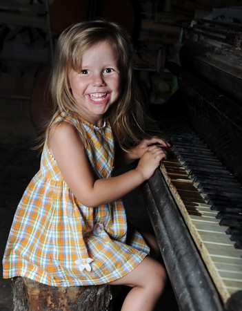 Funny girl playing on an old piano photo