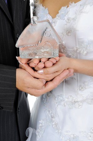 hypothec: House in the hands of the newlyweds. Isolated on white background Stock Photo
