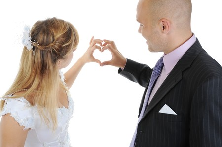 Newlyweds make heart fingers. Isolated on white background photo
