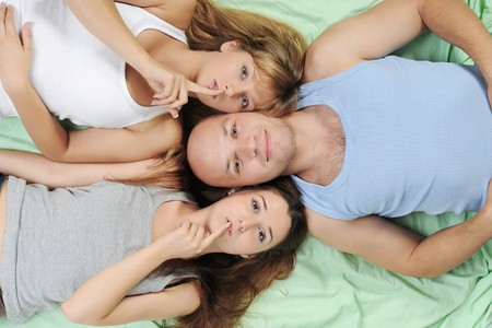 Two beautiful women and man lying on the bed photo