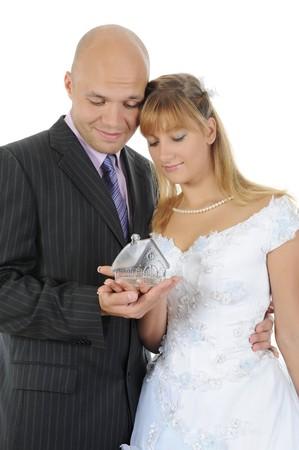 Casa de muñecas en manos de los recién casados. Aislados en fondo blanco  Foto de archivo - 7701601
