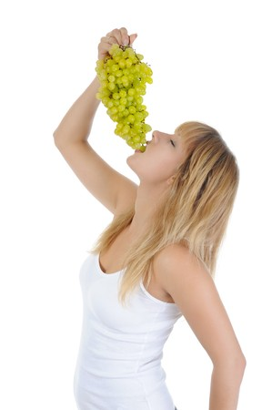 blonde girl eating grapes. Isolated on white background photo