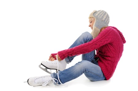 Beautiful girl puts on skates. Isolated on white background Stock Photo - 7701523