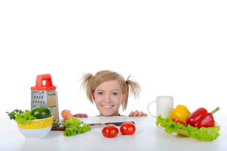 smiling blonde looks for fresh vegetables. Isolated on white background photo