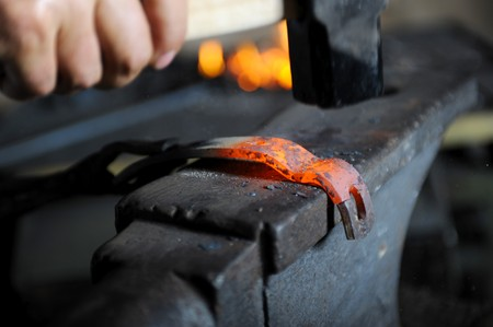 Blacksmith forges a hot spear on the iron anvil photo