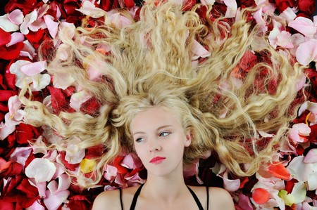 Portrait of a beautiful blonde in rose petals photo
