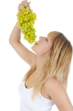 young blonde girl eating grapes. Isolated on white background photo