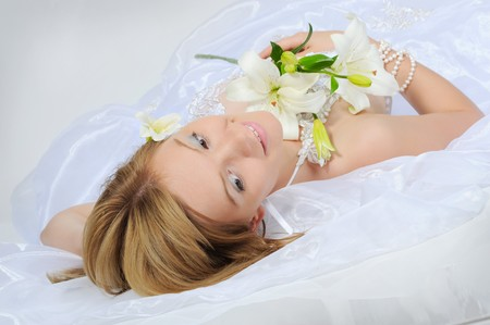 young bride with a bouquet of lilies on a gray background photo