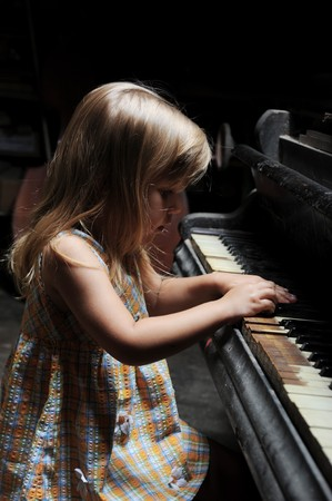 little girl playing on an old black piano photo