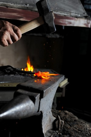 Making a decorative element in the smithy on the anvil photo