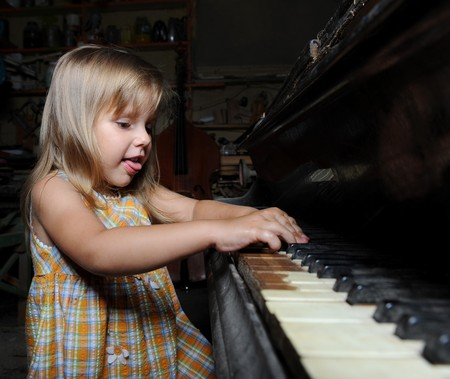 Little girl playing on an old black piano Stock Photo - 7799763