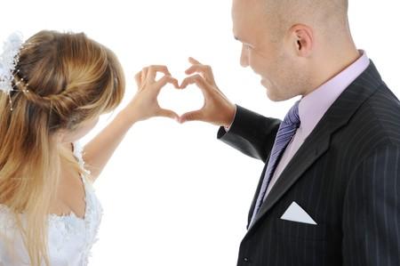 Newlyweds make heart fingers. Isolated on white Stock Photo - 7799740