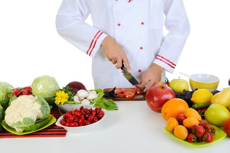 Chef cuts the vegetables. Isolated on white photo