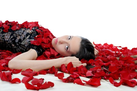 Portrait of young brunette in red rose petals. Isolated on white background Stock Photo - 7799821