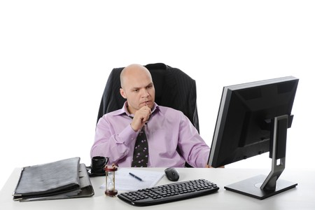Businessman sitting before a computer. Isolated on white background photo