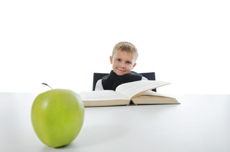 boy at the desk reading a book. Isolated on white background photo