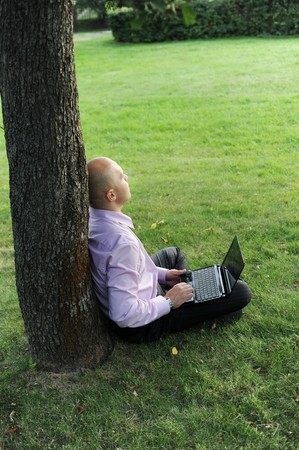 man with laptop sitting near a tree in the park Stock Photo - 7890749