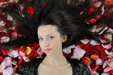 Portrait of beautiful brunette in red rose petals photo