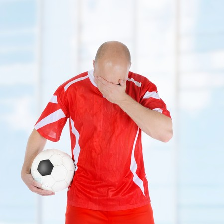 Upset soccer player in the red form.  photo