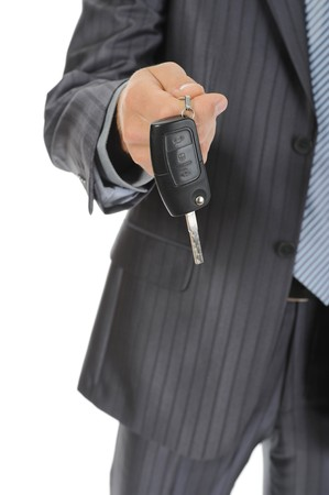 Businessman gives the keys to the car. Isolated on white photo