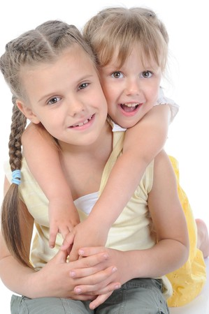 Portrait of two happy sisters. Focus on the front of the girl. Isolated on white background photo