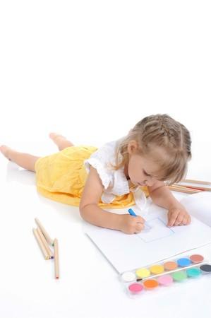 Girl draws on the album. Isolated on white background photo