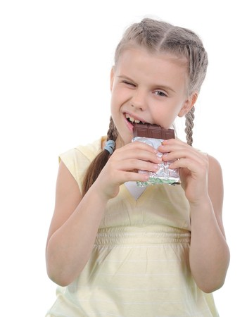 Little girl eating chocolate. Isolated on white background photo
